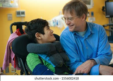 Smiling father sitting next to disabled son in wheelchair by  hospital bed,  talking  together