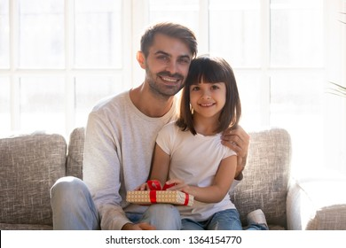 Smiling father small adorable daughter sitting on couch in living room posing looking at camera. Holidays celebrations, father day congratulations, handmade creative surprises family portrait concept