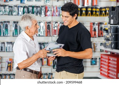 Smiling father and son buying cordless drill in hardware store
