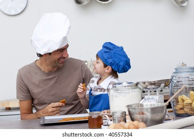 Smiling father and son eating home-made cookies in the kitchen