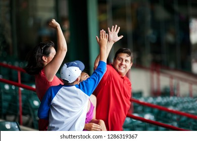 Smiling father and son high fiving each other at a baseball game.