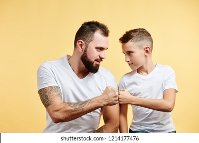 smiling father and son with pleasant smile give fist bump to each other