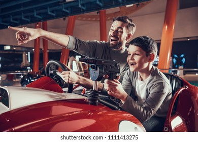 Smiling father and son sitting on toy car. Spending holiday together with family. Entertainment center, mall, amusement park. Family rest, leisure concept.
