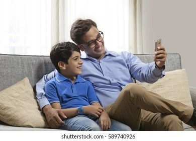 Smiling father and son sitting on sofa using mobile phone