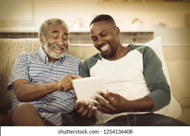 Smiling father and son using digital tablet in living room at home