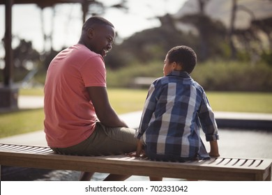 Smiling father talking to son near pool side