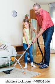 Smiling father teaching cute little daughter vacuuming during clean-up at home