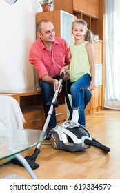 Smiling father teaching little daughter vacuuming during clean-up at home