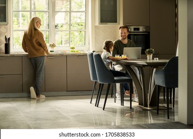 Smiling father working on laptop computer and talking to little cute daughter sitting at table in kitchen. Loving mother looking at them cooking at kitchen counter