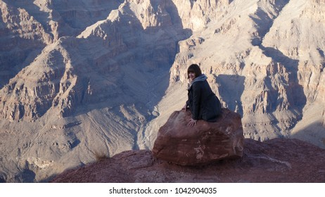 Smiling fearless girl is sitting at the edge of Grand Canyon and looking back (AZ, USA)