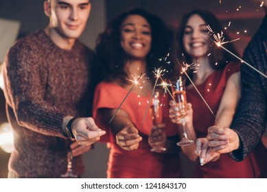 Smiling and feel happy. Multiracial friends celebrate new year and holding bengal lights and glasses with drink.