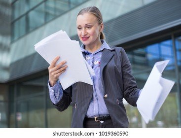 Smiling female architect with paper documents in the hand outdoors