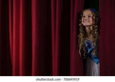 Smiling female artist peeking through the red curtain