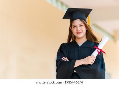 Lächelnde asiatische Studentin im akademischen Gewand und Abitur mit Diplom