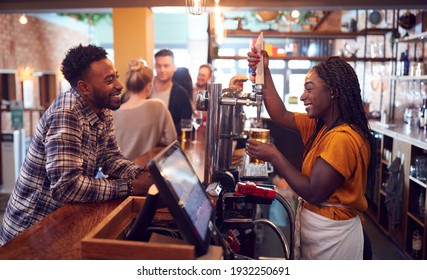 Smiling Female Bartender Behind Counter Serving Female Customer With Beer