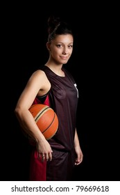 Smiling female basketball player, in black background