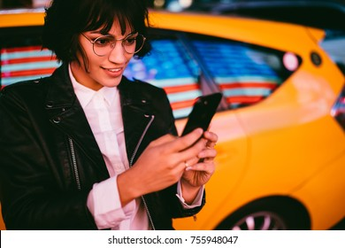 Smiling female blogger reading messages from followers spending time at night city, positive hipster girl in stylish eyewear using application on smartphone standing on New York street in evening