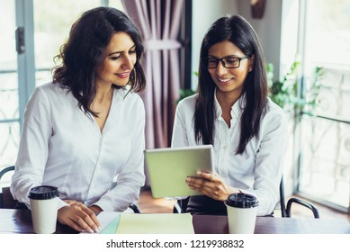 Smiling female business colleagues examining data on touchpad. Young Caucasian and Latin American businesswomen sitting at table and using digital tablet in office. Teamwork concept
