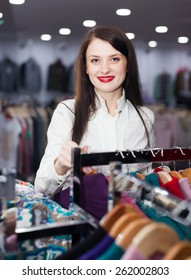 Smiling female buyer choosing clothes at fashionable shop