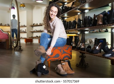 Smiling female buying winter women shoes in a shoe shop