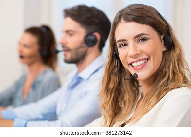 Smiling female call centre operator doing her job with a headset while looking at camera. Portrait of happy woman in a callcenter smiling and working. Portrait of happy smiling support phone operator.