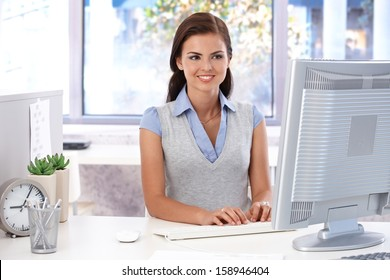 Smiling female casual office worker sitting at desk in bright office, using computer.