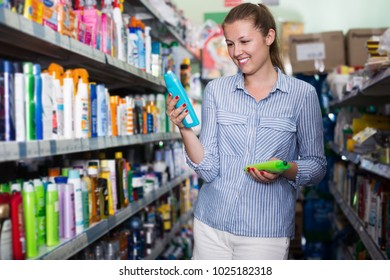 Smiling female choosing shampoo for hair at the supermarket