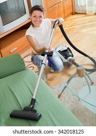 Smiling female cleaning sofa with hoover at living room