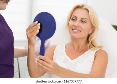 Smiling female client satisfied with result after cosmetic procedure. Beautiful woman sitting on couch near doctor, looking at mirror and examining skin. Concept of beauty and skin care.