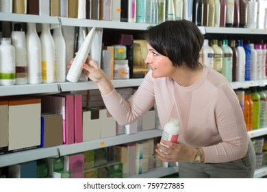 smiling female customer looking conditioner for hair in beauty store