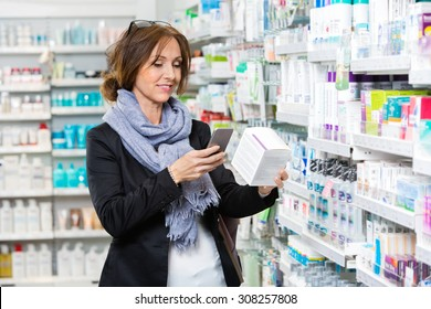 Smiling female customer scanning product through cell phone in pharmacy