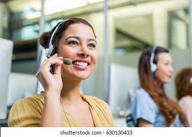 Smiling female customer service executive talking on headset at desk in office