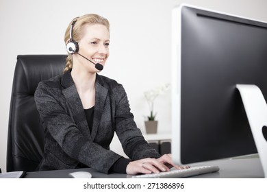Smiling Female Customer Service Representative Typing on Computer While Sitting at her Office.