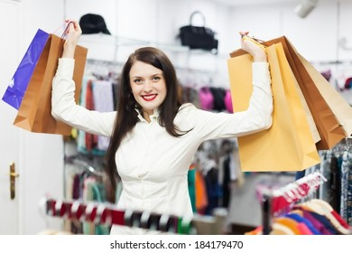 Smiling female customer with shopping bags at clothing store