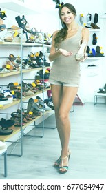 Smiling female customer showing desired shoe in boutique