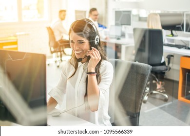 Smiling female customer support operator with headset working in office