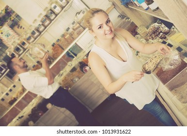 Smiling female customer taking with scoop cereals sold by weight in organic shop