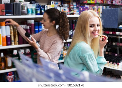 Smiling female customers looking at shelves with cosmetic products