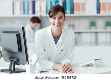 Smiling female doctor at the clinic reception desk, healthcare and professionalism concept