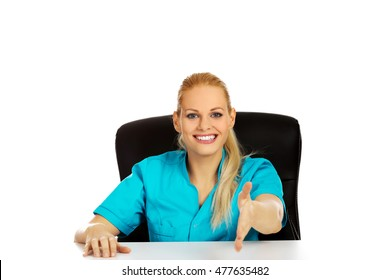 Smiling female doctor or nurse sitting behind the desk with hand redy to handshake