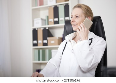 Smiling Female Doctor Relaxing at her Office While Calling to Someone Using a Mobile Phone