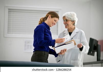 Smiling female doctor speaking with a pharmaceutical representative inside a hospital.
