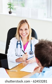 Smiling female doctor writing a prescription for her patient in the office looking at the camera
