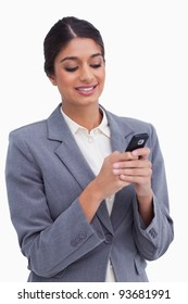 Smiling female entrepreneur writing text message against a white background