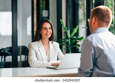 Smiling female financial adviser talking with a customer.