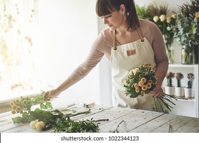 Smiling female florist working at a table in her flower shop arranging a bouquet of roses