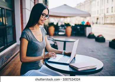 Smiling female freelancer satisfied with online business checking banking account via laptop, smart student i eyewear learning information during online courses spending time on cafe terrace with wifi