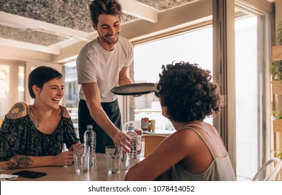 Smiling female friends at a cafe with waiter serving water. Two young women sitting at a restaurant.