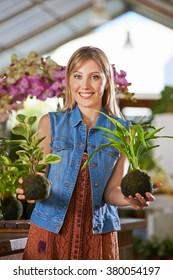 Smiling female gardener holding two kokedama in nursery in her hands
