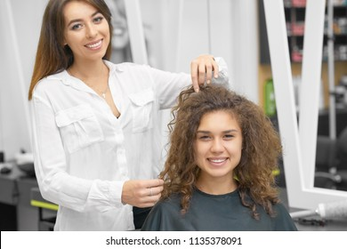 Smiling female hairstylist working with young curly client, looking at camera, laughing. Hairdresser wearing white casual shirt, girl is covered with special black cape. Posing in whitish beaty salon.
